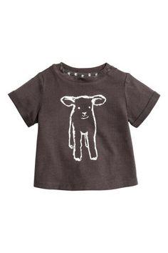 プリントデザインTシャツ: BABY EXCLUSIVE/CONSCIOUS。オーガニックコットンを使用した、ソフトなジャージー素材のTシャツ。フロントにプリントのデザイン入り。ショルダーにスナップボタン付き。袖口の折り返しが縫い付けられた半袖。