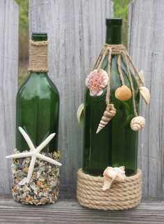 Add a touch of coastal charm to any room with this unique set of two wine bottles, decorated with crushed shells, larger seashells, starfish, jute, and rope. Set of Two: One wine bottle is 750ml, 11 1/2 Tall, 3+ in. Diameter w/ Decor. The other is notably larger: 1.5L, 13 Tall,