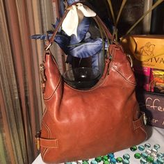 Michael Kors Leather Hobo Bag Please view all pics please bag has minor damage. Authentic MK Bag- Sz 13x13- Tan color- Genuine leather- accented buckles on each side- few stains inside interior- few scratches from normal wear- there's a very small hole on bottom left of the bag it's only on one side pls view pic #4- other than that it's ok. MICHAEL Michael Kors Bags Hobos