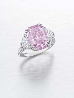 A SUPERB COLORED DIAMOND AND DIAMOND RING Set with a cut-cornered rectangular-cut fancy intense purplish pink diamond, weighing approximately 5.29 carats, flanked on either side by a half moon-cut diamond, mounted in platinum With report 5171023436 dated 17 February 2015 from the Gemological Institute of America stating that the diamond is fancy intense purplish pink, natural color, VS2 clarity
