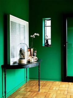 Emerald room with black console table, leaning artwork, and an orchid