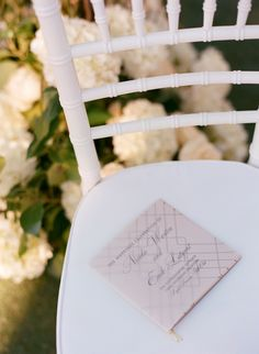 Lovely white chairs for the guest at the ceremony. | Chairs by Niche Event Rentals | Programs by Luster Designs | Photography by Carrie Patterson Photography #AnnaLuciaEvents #CarriePattersonPhotography