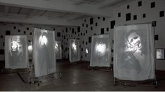 Christian Boltanski, Reflection, 2000, 400 black mirrors, 9 wheeled racks with suspended transparencies on cloth sheets. Each rack: 83 x 52 x 20 in. (210.8 x 132.1 x 50.8 cm)