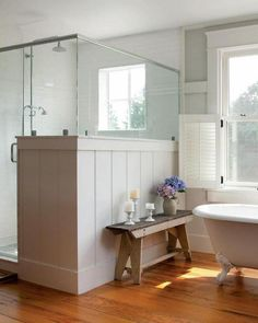 farmhouse bathroom. Love the large standup shower , lovely white walls, and claw foot tub. I'd probably go with tile over wood though