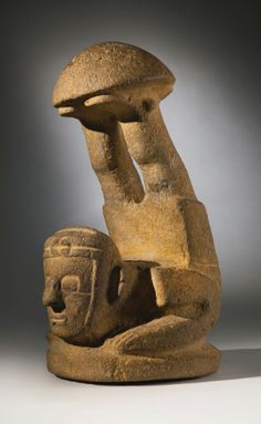 Maya Stone Figure, Pacific Slope region Late Preclassic/Protoclassic, ca. 300 B.C-AD. 300 the ''mushroom' stone in the form of the acrobat figure, with legs sharply thrown up and supporting the domed cap on both feet, with squared torso and arms, large squared eyes and wearing a turban knotted on the forehead; in gray-tan basalt. Height: 14 1/2 in (36.8 cm)