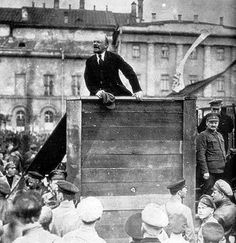 Vladimir Lenin, leader of the Bolsheviks, speaking at a meeting in Sverdlov Square in Moscow, with Leon Trotsky and Lev Kamenev adjacent to the right of the podium