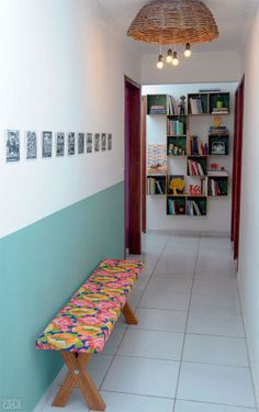 """A faixa colorida conduz o olhar. """"Pintamos só metade de uma das paredes para não sufocar o ambiente"""", explica a blogueira Ana Medeiros. Os 11 nichos que formam a estante foram encomendados a um artesão, que se valeu de duas chapas de OSB com o fundo pintado de verde para produzi-los."""