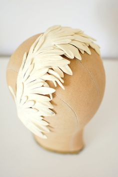 the best vintage 1950s headband/fascinator Ive come across. everyone wears those feather and rhinestone combs these days - heres something truly different for your big day. gorgeous ivory felt in layers upon layers over a velvet band gives the illusion of fluttering wings. studded rhinestones add subtle sparkle. one size fits all. is 60+ years old and ivory but is in overall clean, excellent condition.