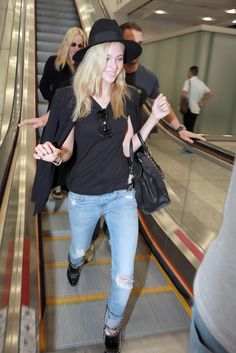 Arriving in Hong Kong, Nicola Peltz chose a casual look: black hat, blazer and T-shirt with distressed jeans. [Photo by ChinaFotoPress/Getty Images]