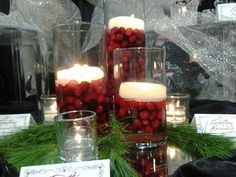 Amazing winter wedding centerpieces!  cranberries and white floating candles and some pine branches.
