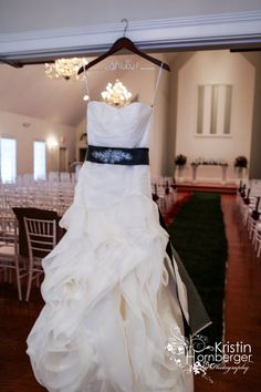Shelbi + Joey: Shelbi's gorgeous dress by Vera Wang. Love the gorgeous belt.  Ceremony at The Chapel at Ritz Charles, Carmel, IN  (and super cute hanger is awesome for pictures!) #Wedding #Dress #Hanger #Indy