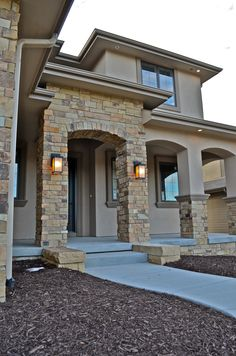 Exterior Stone & Stucco Entrance anchored by clean line lanterns.