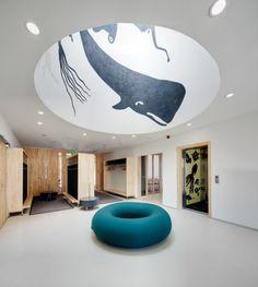 House of Children in Saunalahti / JKMM Architects, cubbies, coat hootks, mural, round skylight, wood casework