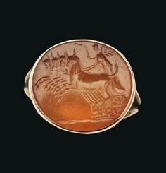 A ROMAN CARNELIAN INTAGLIO RING   CIRCA 1ST CENTURY B.C.   The oval stone with winged female figure, probably Victory, driving a quadriga, holding a whip in her raised left hand, the horses galloping to the left, on groundline, in modern ring setting  Intaglio 5/8 in. (1.6 cm.) wide