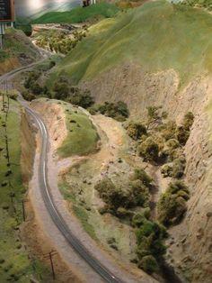 Train tracks meander through highly realistic hillside scenes.