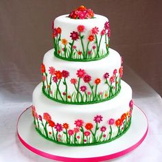 Fuchsia and neon orange daisies line this cheery cake, fit for a garden party wedding.