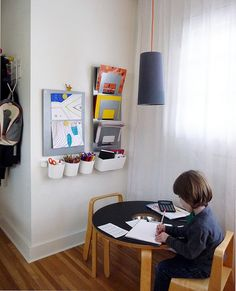 Simple space, with supplies, paper access, display area and work space, all in a corner of a room. Notice lighting.