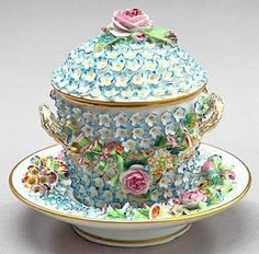 A fine Jacob Petit~Paris~Blue and white~Schneeballen porcelain trembleuse~with applied floral garlands~The set comprised of a well underplate~A two-handled beaker and a domed cover~Circa third quarter 19th century