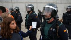 A girl showing a ballot to an anti-riot Civil Guard in an image that reminds the youth revolution of may 68.