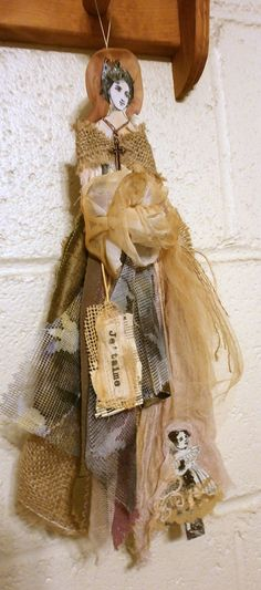 made from tattered fabric and burlap.  Doll is carrying a smaller child doll near skirt bottom.  14 inches tall. has tag and handmade rose at waist.  Wears