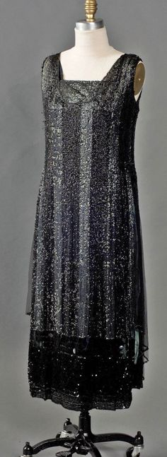 Evening dress, American, ca. 1925-28. Front & back panels covered w/sequins on silk tulle net. Most are black but also 3 vertical stripes of opalescent green & an insert at front neckline. This floats over dark blue silk satin. Under all, a wide fitted petersham belt holds dress firmly at hipline to blouse slightly. Below gathering are black silk tulle godets (triangle inserts) on each side seam between front & back panels. Smith College Historic Clothing