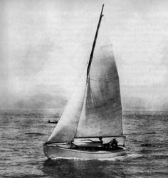 A black and white photo of a wooden sailboat with the mainsail and jib raised.