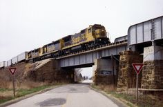 https://flic.kr/p/NjDt7Q | Yield to the Santa Fe | An eastbound Santa Fe intermodal zips above Illinois Route 5 in Cameron on its way to Chicago. B40-8 7442 led SD45 5401 and GP50 3838 through the dreary Illinois countryside with the hotshot traffic.