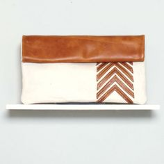White Arrow Clutch Caramel Front. Sseko Designs uses fashion to provide employment and scholarship opportunities to women pursuing their dreams and overcoming poverty.
