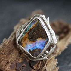 Full of depth and movement, this is just an amazing piece of boulder opal from Australia.... With deep rivers of blues and purples, this ring is bright and bold. Featuring my signature leaf impressions band, this ring also is encircled in lovely branches, dew drops and leaves... An organic treat for the nature lover at heart.; Exquisite Blue Purple Boulder Opal Woodland Dance ring by opalwing, $325.00