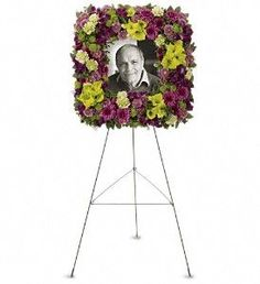 A unique and lovely tribute for the service, this contemporary square easel wreath of purple and green flowers is a gift of caring expressed with beauty and style.        $185.00