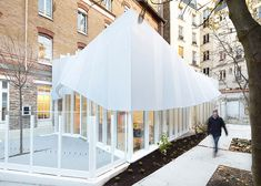 A folded fabric canopy helps to shade the interior of this glazed extension to a nursery in Paris.