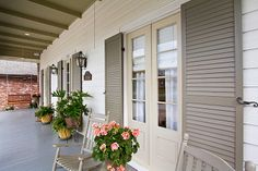 Front porch; grey green shutters; French doors; rocking chairs; gas lanterns