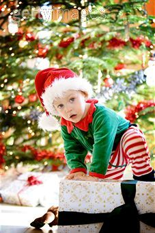 A sweet toddler boy wearing a Santa hat and festive Christmas pyjamas, climbs mischievously on top of a large wrapped Christmas gift.