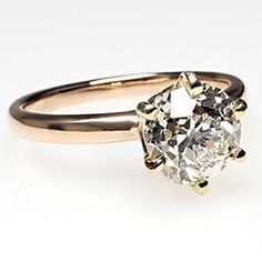 This magnificent antique engagement ring features a large old European cut diamond (1.47) set in a timeless 6 prong style head. The ring is crafted of solid 14k yellow gold and is from the early 1900's.