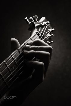 Hand of a Guitarist close-up with only neck and head of guitar in image