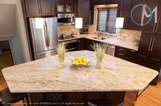 The large, uniquely shaped island is the focal point of this kitchen. Materials: Cielo de Oro  Edges: ¼ Round