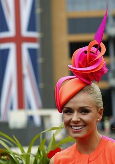 Neon red-orange and fuchsia fascinator that looks like it has a little pink sail on top.