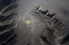 """Greenpeace activists stand next to massive letters delivering the message """"Time for Change: The Future is Renewable,"""" next to the hummingbird geoglyph in Nazca in Peru, Dec. 8, 2014. Greenpeace activists displayed the message, which can be viewed from the sky, during the climate talks in Peru, to honor the Nazca people, whose ancient geoglyphs are one of the country's cultural landmarks -  can't believe they thought that was a good idea. sad."""