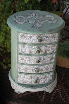 This rarely seen vintage jewelry box, has been transformed into a work of art. Layers of mint and sage paint have been painted, moderately distressed, then waxed with a European Paste Wax. A very French wallpaper design decorative paper has been applied to the drawer fronts, and metallic pewter covered buttons are applied to the drawer handles for a chic look. Five open drawers which have a fushia velveteen liner, will give you ample storage for all of your jewelry treasures! The dimensions…