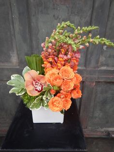 Great movement arrangement, with flair. Orange Snap Dragons, Orange Spray Roses, Palmetto