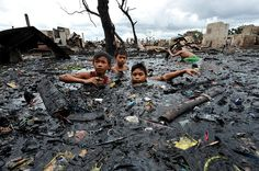 Children look for salvageable materials while submerged in water filled with charred items and ash after a fire gutted a sprawling shanty town in Malabon, part of Metro Manila, shortly before midnight on August 7, 2010.