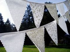White bunting...so pretty! I'm imagining something similar but with pretty vintage fabrics... (image from Etsy)