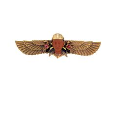 Egyptian Revival Gold, Carved Jasper, Ruby and Enamel Brooch  Centering a stylized pharaoh with carved jasper visage and gold and black and yellow enamel headdress, flanked by serpents accented by 2 round rubies and patterned wings, approximately 6.4 dwt.
