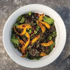 Crispy baked kale, sweet roasted squash, and peppery arugula and watercress are combined with pumpkin and pomegranate seeds in this colorful salad.