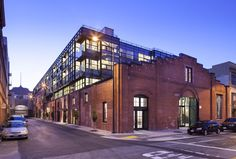 A sleek glass structure was inserted into the original masonry building, juxtaposing materials and volumes.
