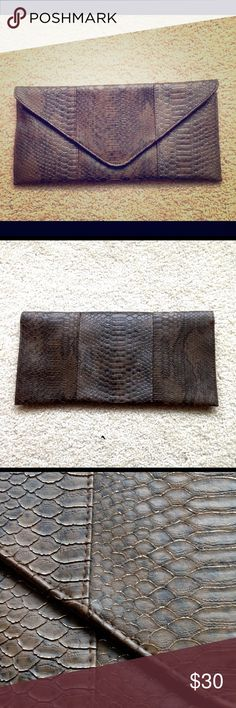 Large Clutch Dark brown faux snake skin clutch, very large with dimensions of about 15in. long and 6-7in tall. Gold detail on the outside and small inner pockets for storage. JustFab Bags Clutches & Wristlets