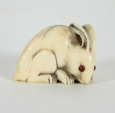 A Japanese carved ivory netsuke, early 19th Century, depicting a rabbit, signed beneath, 3cm high