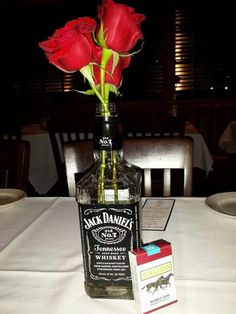 Gangster party centerpiece - save your favorite liquor bottles and add flowers. Cheap but chic centerpieces