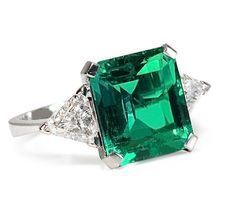 this is EXACTLY what I want. Sonata: 6.55 ct Emerald Diamond Ring and for the bargain price of $139,000.... GAH! But if the look were available for less I'd swoon for a nice giant radiant cut emerald with trillion cut diamond sidestones in a platinum or white gold setting.