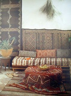Hang ornamental rugs at a lower level to display, with paintings hung up above.